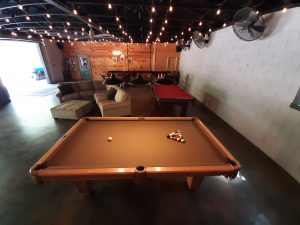 interior of lodge, view featuring pool table in foreground and couches in background