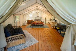 interior of luxury glamping tent, showing armchair, bed, and furnishings